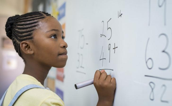 Girl learning about addition on a white board